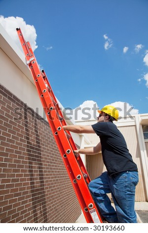 Construction worker climbing up a ladder to the roof of a building. - stock photo