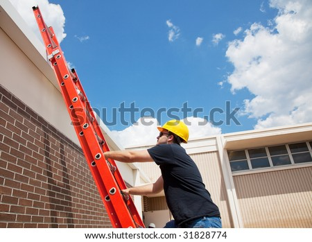Construction worker climbing up to the roof of a building.  Wide view with lots of room for text. - stock photo