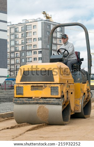 Construction worker compacting sand with vibration roller - stock photo