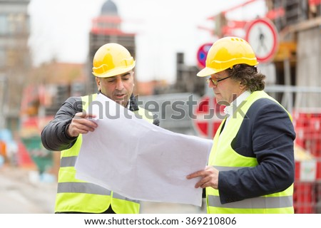 Construction worker contractors checking office blueprints - stock photo