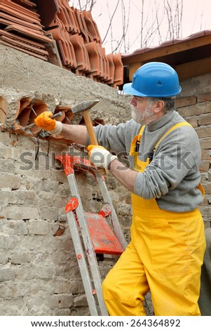 Construction worker demolishing old brick wall with chisel tool and hammer - stock photo