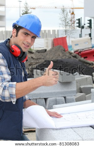 Construction worker giving the thumbs up - stock photo