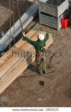 Construction worker guiding a crane operator in lifting pieces of scaffolding.