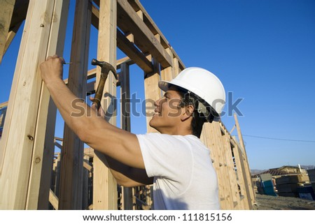 Construction worker hammering at construction site