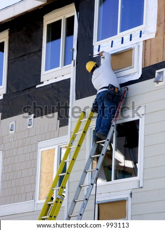 Construction worker hanging siding on new apartment building under consctruction.