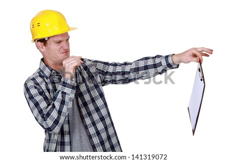 Construction worker holding a distasteful clipboard - stock photo