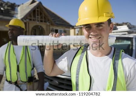 Construction worker holding blueprint - stock photo