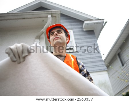 Construction worker holding blueprints. Residential house in the background - stock photo
