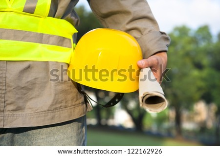 Construction worker holding hat and plans