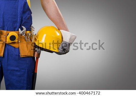 construction worker holding helmet on gray background with copy space - stock photo