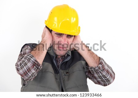 Construction worker holding his hands over his ears