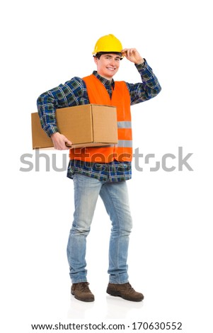 Construction worker holds carton box under one's arm. Full length studio shot isolated on white.