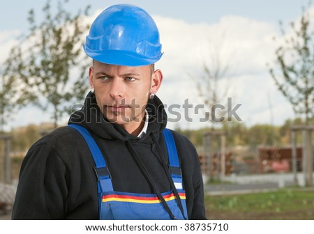Construction worker in blue hard hat standing outdoors
