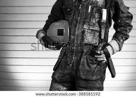 Construction worker in dirty overalls in Finland. The laborer have orange gloves, blue helmet and hammer. Background out of focus and illuminated with flash. Image includes a black and white effect. - stock photo