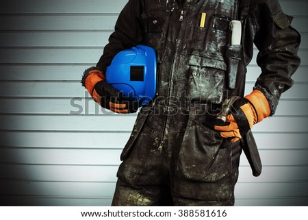 Construction worker in dirty overalls in Finland. The laborer have orange gloves, blue helmet and hammer. Background out of focus and illuminated with flash. Image includes a effect. - stock photo