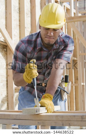 Construction worker in hardhat at work on construction site - stock photo