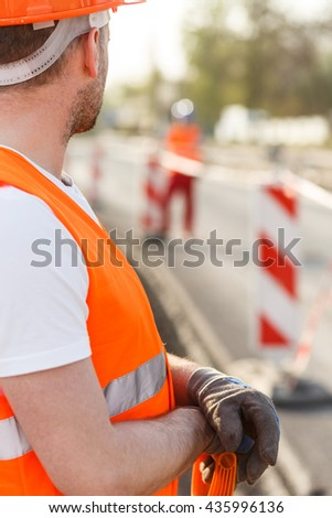 Construction worker in high-visibility clothes on the building site - stock photo