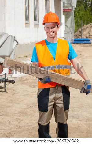 Construction worker in protective workwear holding wooden beam - stock photo