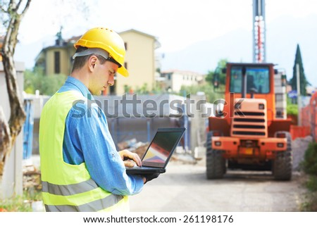 construction worker in safety protective work wear with laptop computer  at construction site in front of loader machinery - stock photo