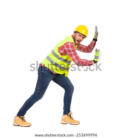 Construction worker in yellow helmet and reflective lime waistcoat pushing white big placard. Full length studio shot isolated on white. - stock photo