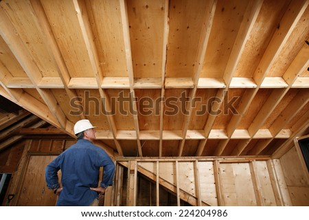Construction worker inspecting home addition. - stock photo