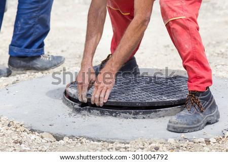 Construction worker installing manhole cover at building site - stock photo