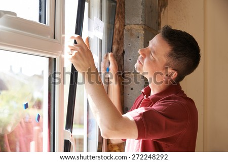 Construction Worker Installing New Windows In House - stock photo