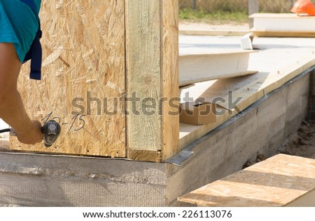 Construction worker installing wall insulation on a new build house, close up of his hand and the corner of the newly laid cement floor - stock photo