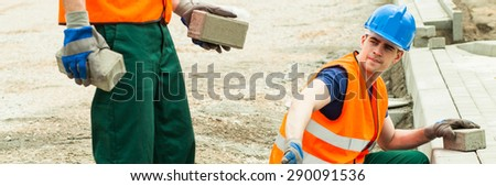 Construction worker is giving the setts to his colleague