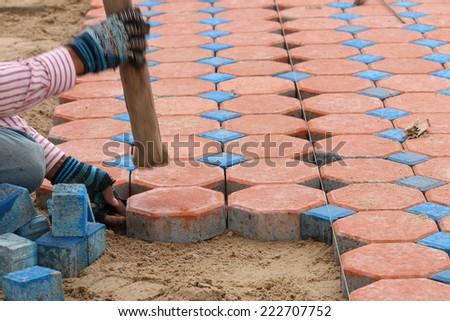 Construction worker is installing the brick foot bath, foot bath jigsaw - stock photo