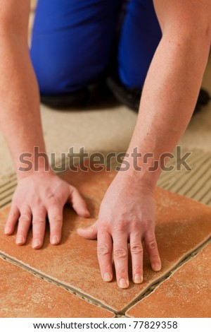 Construction worker is tiling at home - stock photo