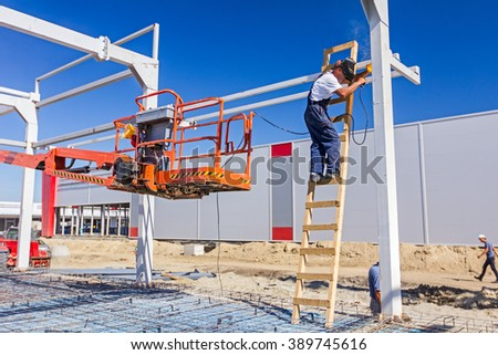 Construction worker is welding metal frame without proper safety equipment on wooden leaders.  - stock photo