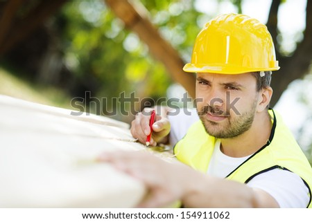Construction worker is working with wooden beam - stock photo