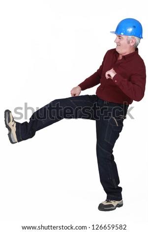 Construction worker kicking something - stock photo