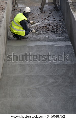 Construction worker level concrete floor with spatula