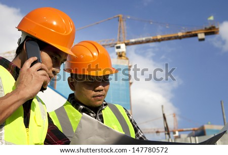 Construction worker looking at blueprint at construction site and one people talking on the phone