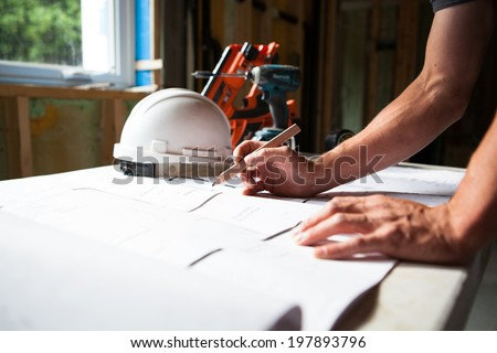 Construction worker looking at blueprints at construction site - stock photo