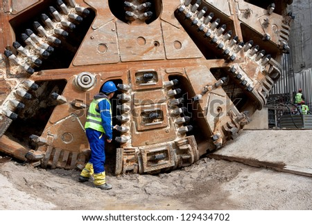 Construction worker looking at tunnel boring machine cutter head - stock photo