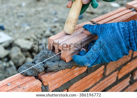 construction worker.  mason bricklayer installing red brick with trowel putty knife outdoors - stock photo
