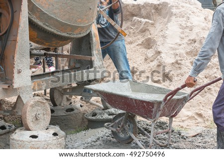 Construction worker mixing ingredients in the concrete mixer at building site