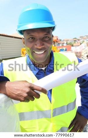 Construction worker on building site with security helmet - stock photo