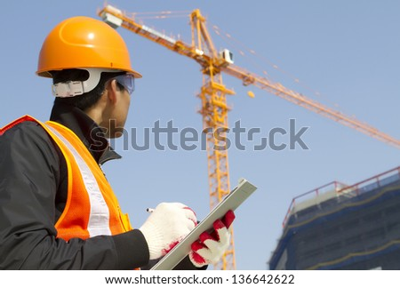 construction worker on location site with crane on the background - stock photo