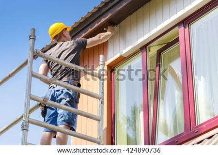 construction worker on scaffolding painting wooden house facade - stock photo