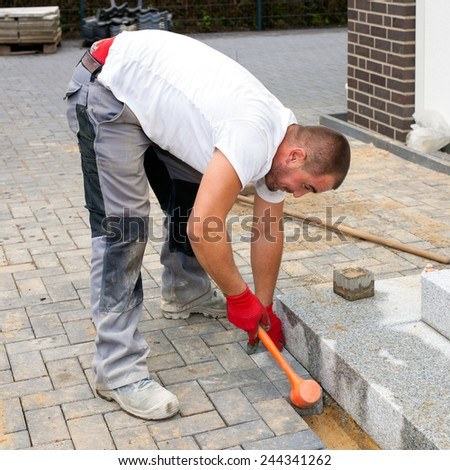 Construction worker placing concrete paving stones to build up a pavement and a terrace in front of a house. - stock photo
