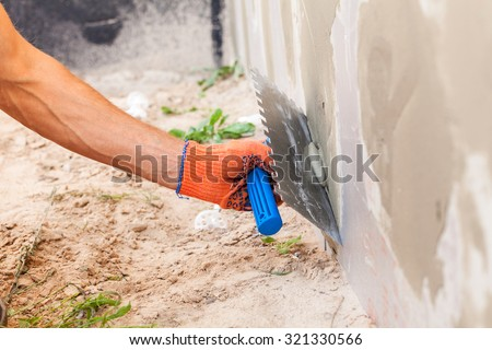 Construction worker plastering a wall and house foundation with trowel - stock photo