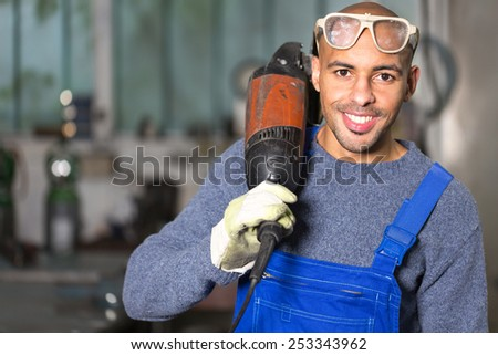 construction worker posing with angle grinder in a workshop - stock photo
