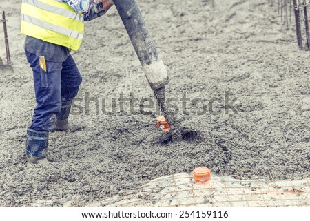 Construction worker pouring concrete, directing the pump and working in foundation - stock photo