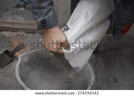 Construction worker pouring the cement to the bucket - stock photo
