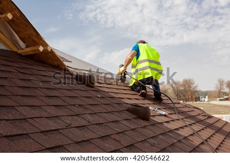 Construction worker putting the asphalt roofing (shingles) with nail gun on a large commercial apartment building development - stock photo