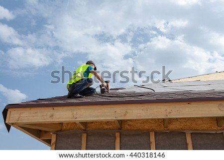 Construction worker putting the asphalt roofing (shingles) with nail gun on a new frame house - stock photo